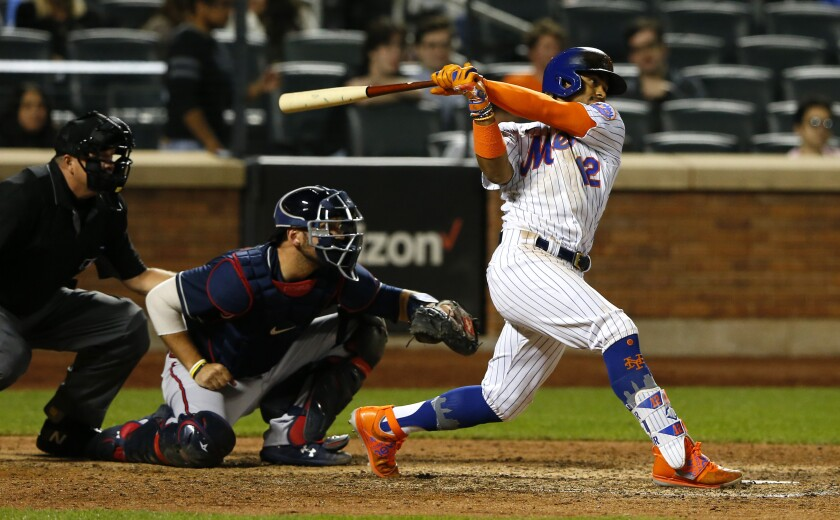 New York Mets shortstop Francisco Lindor (12) follows through on an RBI single against the Atlanta Braves during the eighth inning of a baseball game Wednesday, June 23, 2021, in New York. (AP Photo/Noah K. Murray)