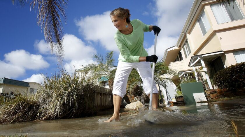 Marylou Alvarez used a broom to help redirect the water pouring past the sidewalk in front of her ap