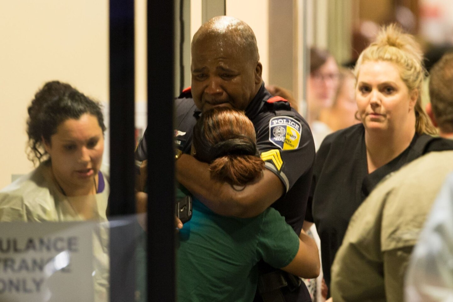 A Dallas Area Rapid Transit police officer receives comfort at the Baylor University Hospital emergency room entrance Thursday, July 7, 2016, in Dallas. Police say one rapid-transit officer has been killed and three injured when gunfire erupted during a protest in downtown Dallas over recent fatal