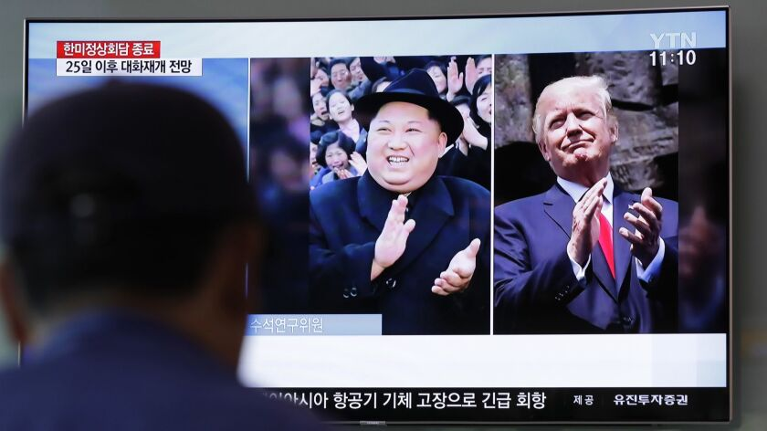 A man watches a TV screen showing file footage of U.S. President Donald Trump, right, and North Korean leader Kim Jong Un, in Seoul, South Korea.