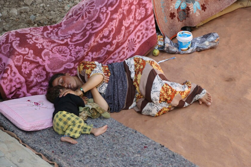 An Yazidi woman and her daughter sleep under a bridge in the northern Iraqi city of Dahuk on Aug. 14.