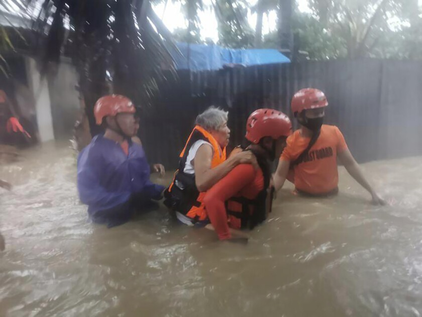 In this photo provided by the Philippine Coast Guard, rescuers evacuate residents to safer ground as floods caused by Tropical Storm Choi-wan hits Maasin City in Southern Leyte province, central Philippines on Tuesday June 1, 2021. The tropical storm has left at least a few people dead and displaced hundreds of villagers in the southern and central Philippines, where it set off flooding and landslides, officials said Wednesday. (Philippine Coast Guard via AP)