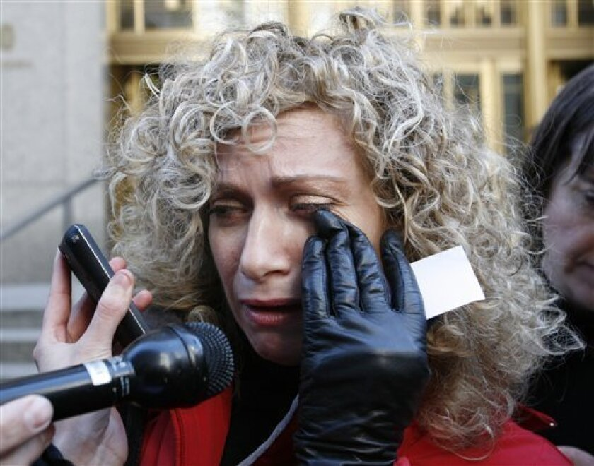 """FILE - In this file photo of March 12, 2009, investor in the Madoff Ponzi scheme, Sharon Lissauer wipes away tears while talking about Madoff outside federal court in New York. A year after Madoff's scheme collapsed - with headlines of $65 billion in losses - investigators are still struggling to measure the full scope and impact of the largest securities fraud in history and are looking at other possible suspects. Losing everything in the Ponzi scheme is """"not a nightmare I'm going to wake up from,"""" one investor, Sharon Lissauer, said in a recent interview. (AP Photo/Mark Lennihan, File)"""