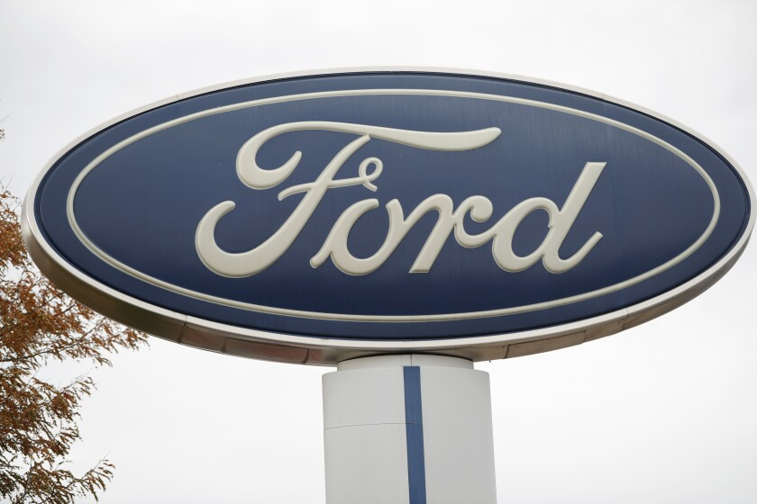 FILE - In this Oct. 20, 2019, file photo, the company logo stands over a long row of unsold vehicles at a Ford dealership in Littleton, Colo. Ford Motor Co.'s profit in 2019 plunged by more than $3.6 billion, weighed down by slowing U.S. sales, the cost of a botched SUV launch and some big pension expenses. (AP Photo/David Zalubowski, File)