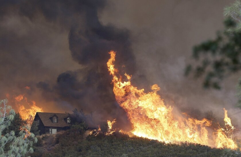 Fires approach a home near Lower Lake, Calif., Friday, July 31, 2015. A series of wildfires were intensified by dry vegetation, triple-digit temperatures and gusting winds. (AP Photo/Jeff Chiu)