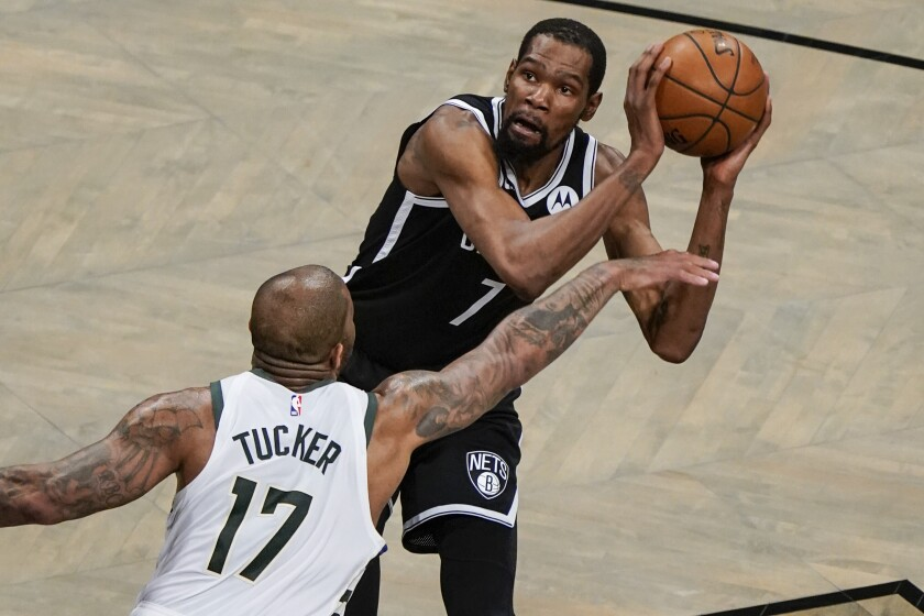 Milwaukee Bucks' P.J. Tucker (17) defends against Brooklyn Nets' Kevin Durant, top, during the first half of Game 7 of a second-round NBA basketball playoff series Saturday, June 19, 2021, in New York. (AP Photo/Frank Franklin II)
