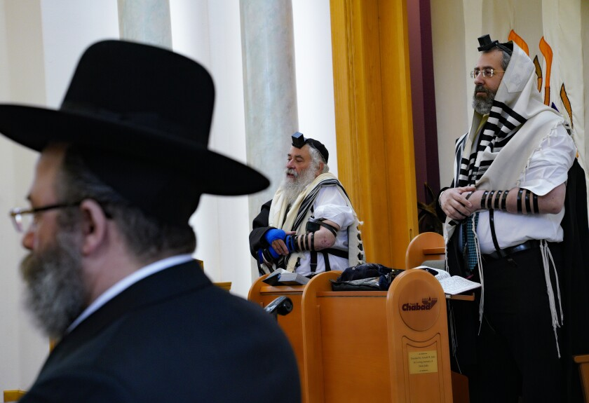 In the sanctuary, Rabbi Yisroel Goldstein and Chief Rabbi of Israel, David Lau, on the right, join in prayer at the Chabad of Poway on Sunday.