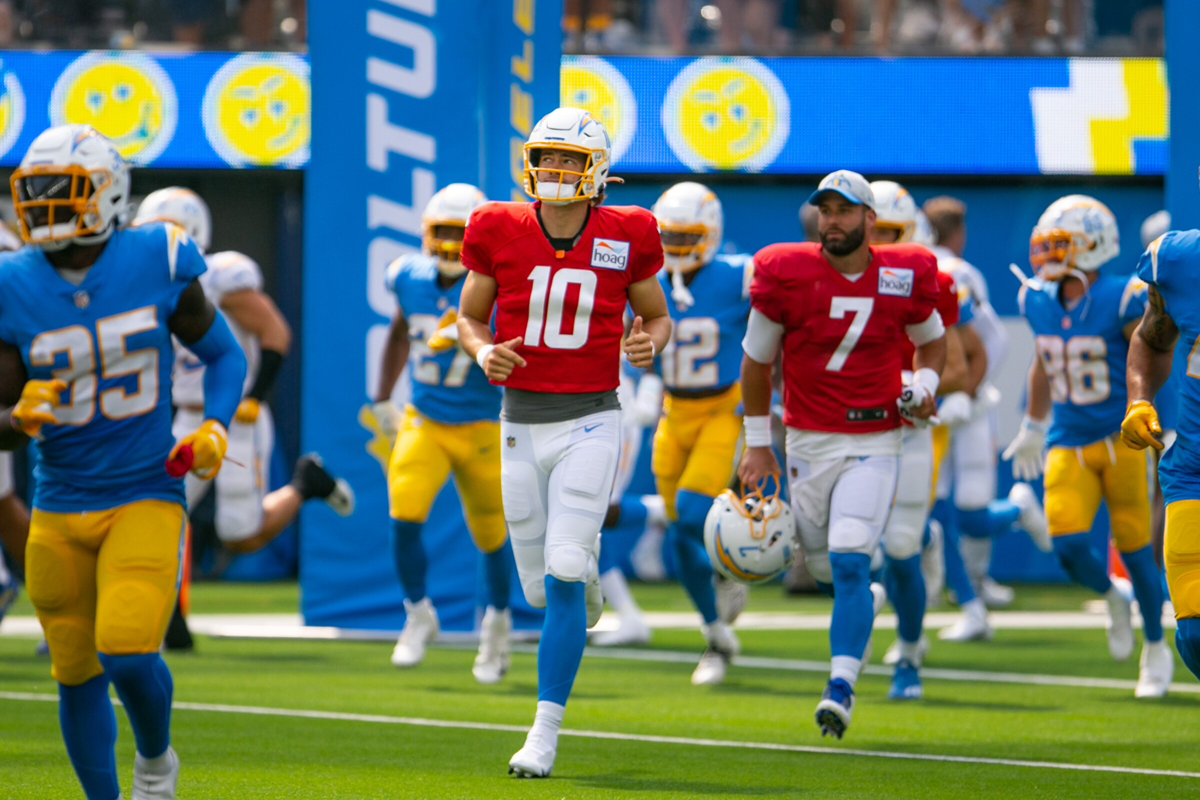 Chargers quarterback Justin Herbert runs onto the field with his teammates before an open practice session at SoFi Stadium.