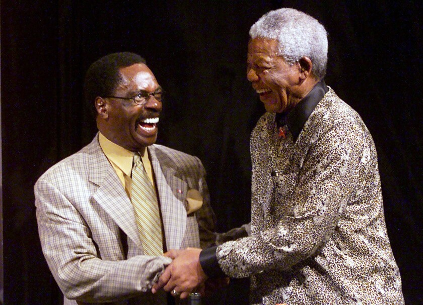 """In a September 2000 file photo, Rubin """"Hurricane"""" Carter, left, shakes hands with Nobel Peace laureate Nelson Mandela during inaugural World Reconciliation Day celebrations in Melbourne, Australia. Carter, who spent 19 years in prison for murder and was released after it was determined he did not get a fair trial, died Sunday at age 76."""