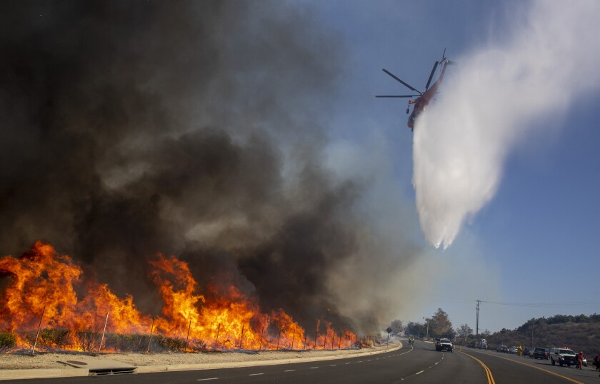 Firefighting helicopter drops water on fire in Simi Valley