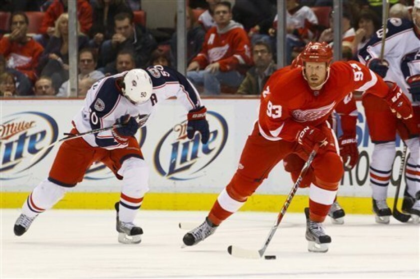 Detroit Red Wings left wing Johan Franzen (93), of Sweden, skates with the puck as Columbus Blue Jackets center Antoine Vermette (50) pursues in the third period of an NHL hockey game in Detroit, on Friday, Oct. 21, 2011. Detroit won 5-2. (AP Photo/Rick Osentoski)