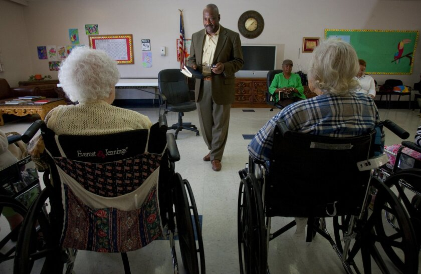 The Rev. Eric Smith helps convalescing seniors at Paradise Valley Manor and Health.  Here, Smith leads the group through hymns.  Nelvin C. Cepeda / Union-Tribune