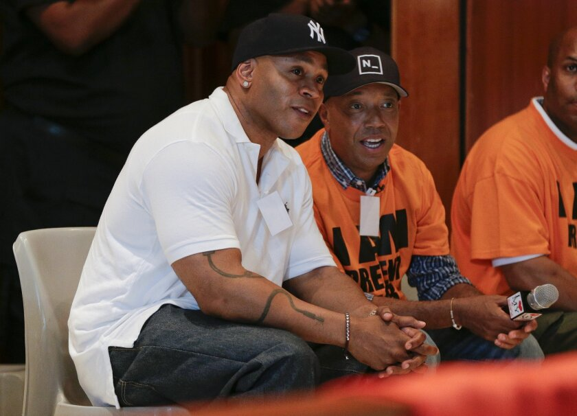 Actor and music artist L.L. Cool J, left, talks with Def Jam co-founder Russell Simmons on a visit to speak with youth at the juvenile detention center of Rikers Island, Thursday, July 31, 2014, in New York. Simmons, founder of the RushCard Keep the Peace initiative, was accompanied by L.L. Cool J
