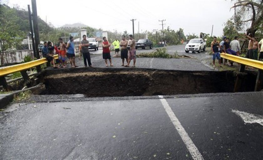 People stand on a destroyed bridge in Samoa's capital Apia, Friday, Dec. 14, 2012, after cyclone Evan ripped through the South Pacific island nation. The powerful cyclone flattened homes and uprooted trees with winds of up to 165 kilometers (100 miles) per hour. Phone lines, Internet service and electricity were down across the country, and the airport was closed. (AP Photo/Seti Afoa)