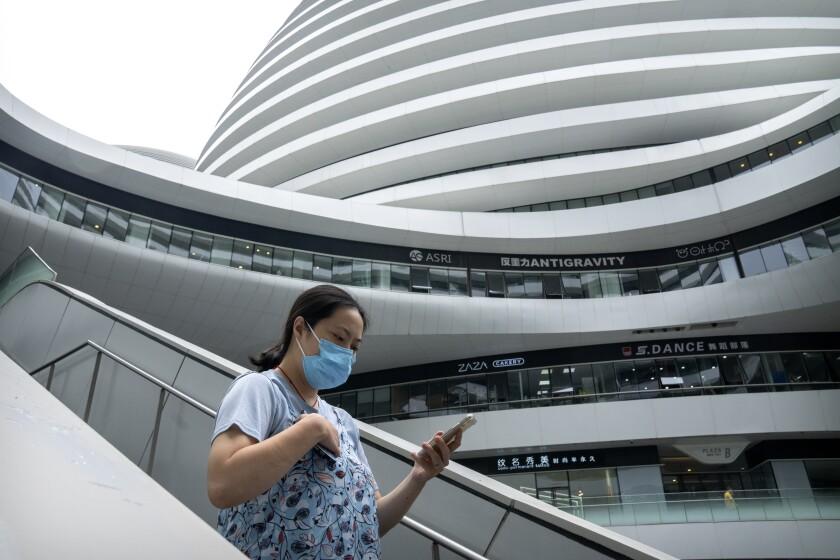 Una mujer con una mascarilla para protegerse del coronavirus camina en un complejo de tiendas y oficinas el martes 27 de julio de 2021, en Beijing. (AP Foto/Mark Schiefelbein)