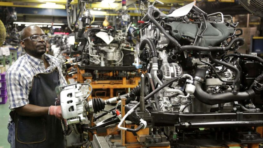 In this Tuesday, June 9, 2015 photo, a Ford Motor Co. employee works on the engine assembly of a 201