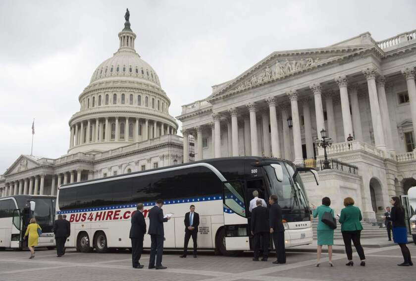 Senators board buses at the U.S. Capitol on Wednesday.