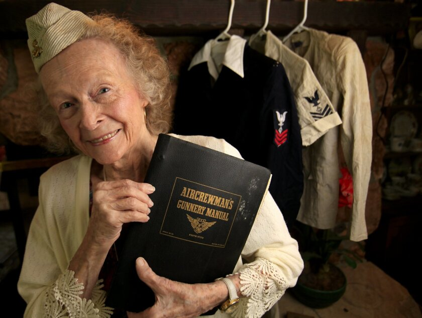 Beverly Newak who was a WAVE (Women Accepted for Volunteer Emergency Service) in the Navy during World War II as a gunnery instructor holds a copy of the aircrewman's gunnery manual she used, stands near her uniforms.