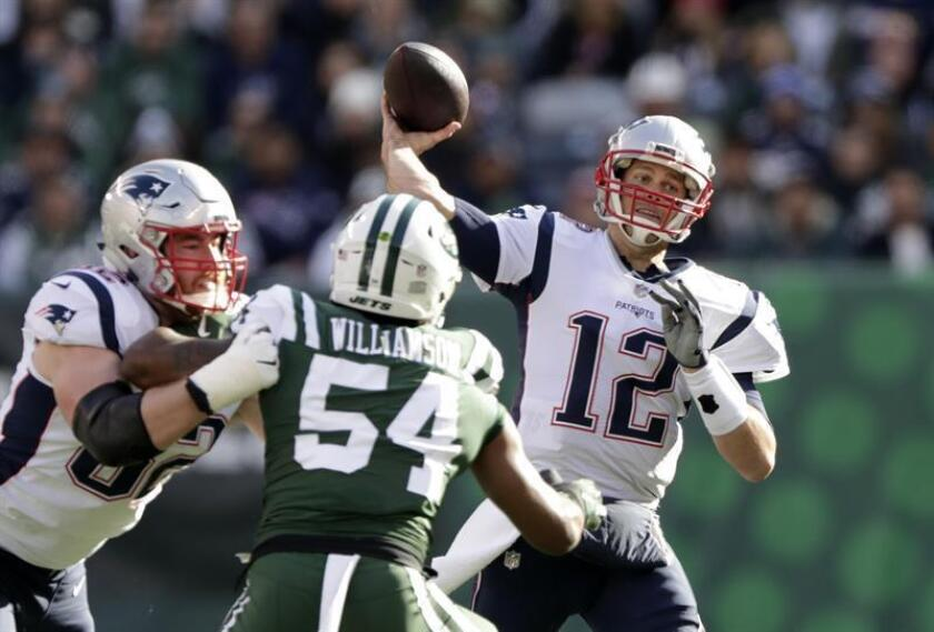 Tom Brady (d), mariscal de campo de los Patriots de Nueva Inglaterra, fue registrado este domingo al hacer un pase frente a la marca de bloqueadores de los Jets de Nueva York, durante un partido de la NFL, en el Estadio MetLife de East Rutherford (Nueva Jersey, EE.UU.). EFE
