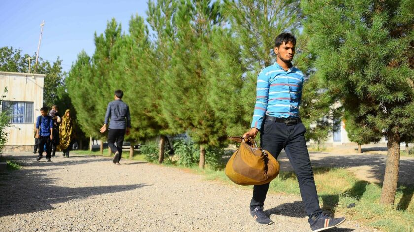 An Afghan man returns to the Afghan province of Herat from Iran, part of an exodus of migrant workers fleeing Iran's economic turmoil.