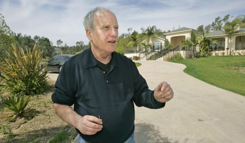 Richard Dreyfuss stands in the driveway of the home in Olivenhain that he and his wife plan to improve. (Charlie Neuman / Union-Tribune)