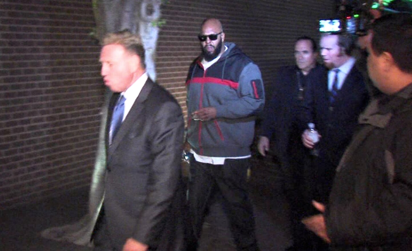 """Marion """"Suge"""" Knight walks into the Los Angeles County sheriff's West Hollywood station early Friday."""