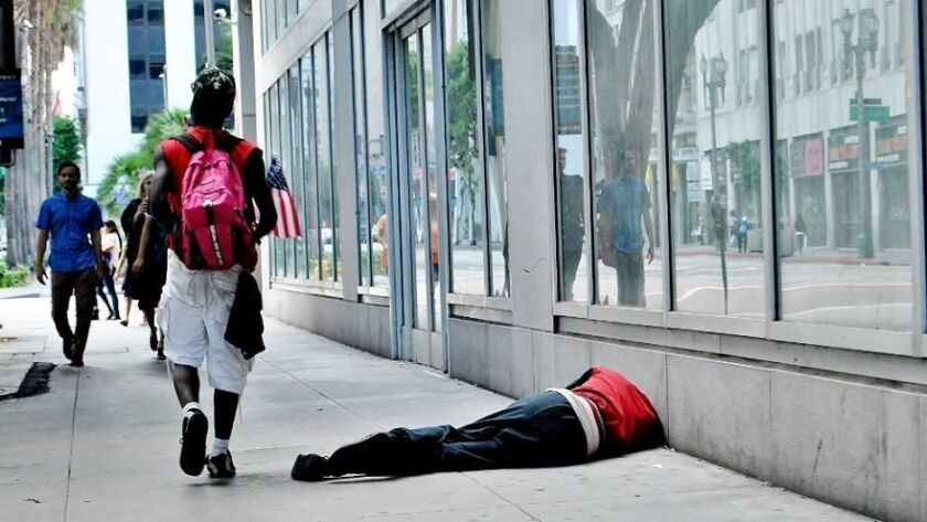 A man with an American flag walks past a sleeping homeless man near the corner of 6th and Broadway in downtown Los Angeles.