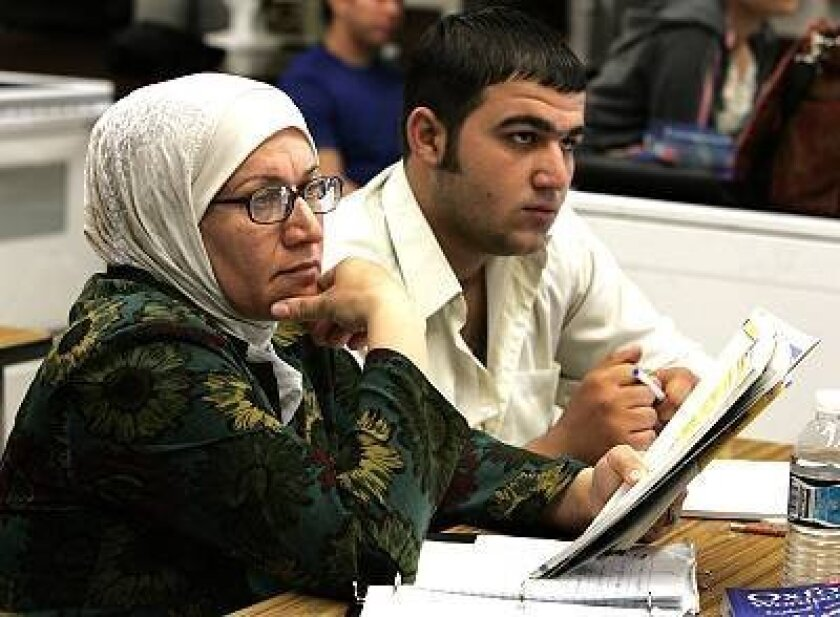 Jamlia Juma (left) and her son Ahmad Albehadili study together in November during their English class at Foothills Adult Education Center in El Cajon. Last fiscal year, 2,356 Iraqis arrived in San Diego County.