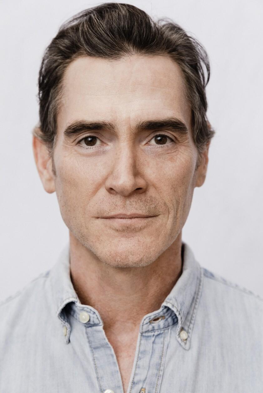 A headshot of a man in a light-blue collared shirt