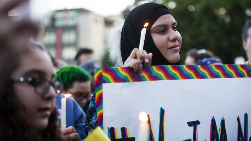"""A Muslim woman holds a candle and a sign that references the hashtag """"#NotInMyName"""" to show that many in the Islamic faith support the LGBT community during a vigil in Seattle on June 12."""