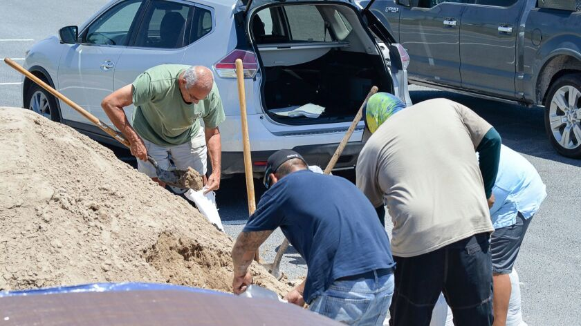 Residents fill sand bags in preparation of the effects of a tropical system on Wednesday, Aug. 23, 2