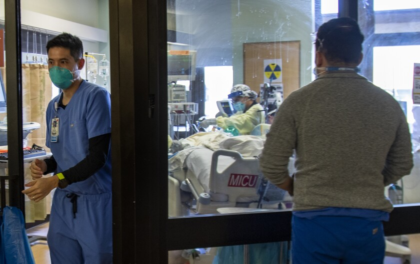 A doctor leaves the room of a COVID-19 patient
