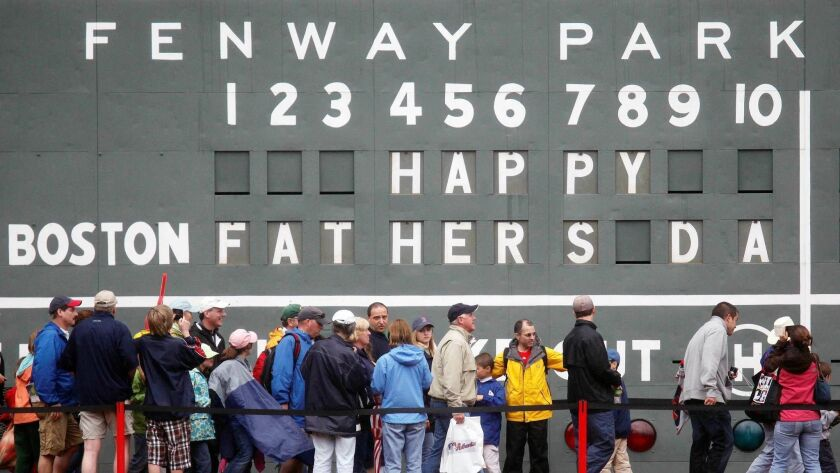 FILE - In this June 21, 2009 file photo, fans tour in front of the scoreboard in Fenway Park in Bost