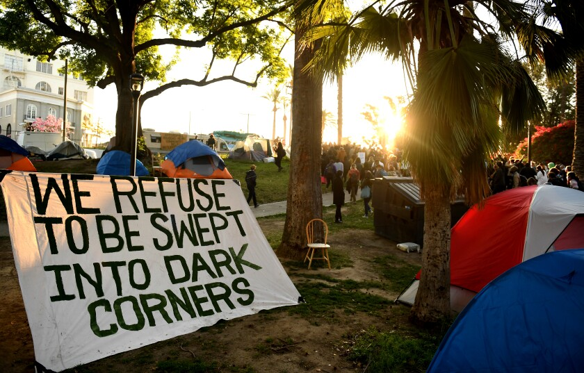 "A sign that reads ""We refuse to be swept into dark corners"" sits among tents for homeless people during a rally."