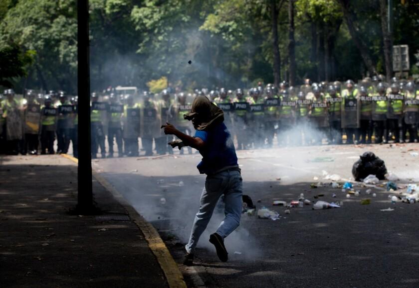 Un estudiante devuelve una lata de gas lacrimógeno que le arrojó la Policía Nacional Bolivariana durante enfrentamientos afuera de la Universidad Central de Caracas, Venezuela. (AP Foto/Fernando Llano)