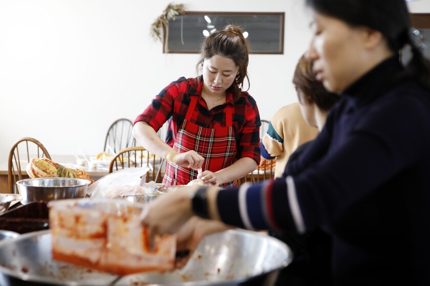 Jessie Kim wraps up the finished kimchi to be taken home by the students at her cooking class in November.