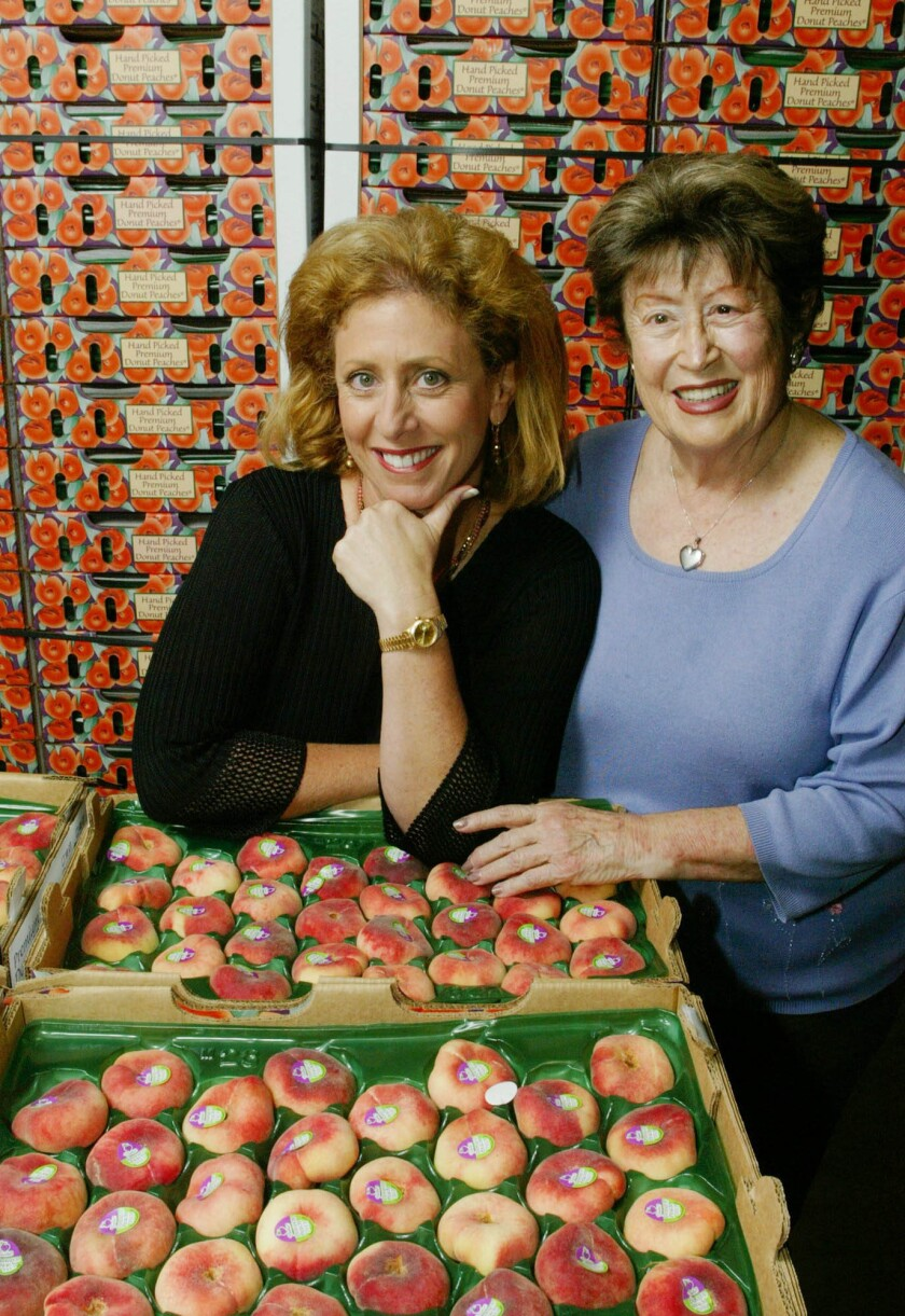 "Frieda Rapoport Caplan, right, and her daughter Karen Caplan, the company president and CEO, with crates of ""donut peaches,"" in Los Alamitos in 2003."