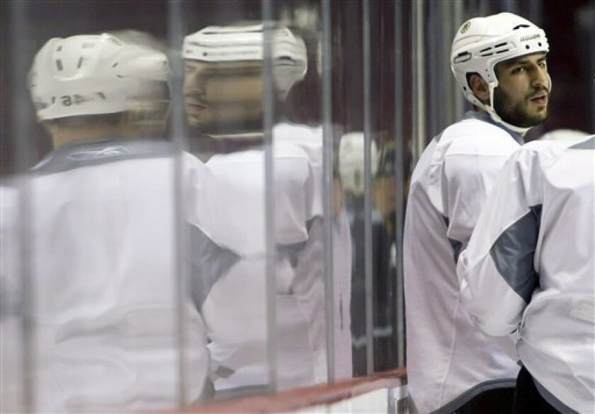 Boston Bruins' Milan Lucic is reflected in the glass during hockey practice in Vancouver, British Columbia, on Tuesday, May 31, 2011. The Bruins face the Vancouver Canucks in Game 1 of the NHL Stanley Cup final on Wednesday. (AP Photo/The Canadian Press, Darryl Dyck)