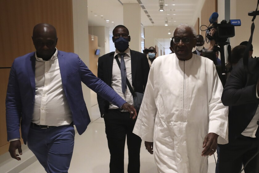 Former president of the IAAF (International Association of Athletics Federations) Lamine Diack, right, arrives at the Paris courthouse, Wednesday, June 10, 2020. A sweeping sports corruption trial opened Monday in Paris involving allegations of a massive doping cover-up that reached to the top of world track and field's governing body. Lamine Diack, 87, who served as president of the body for nearly 16 years, is among those accused of receiving money from Russian athletes to hide their suspected doping so they could compete at the Olympics in 2012 and other competitions. (AP Photo/Thibault Camus)