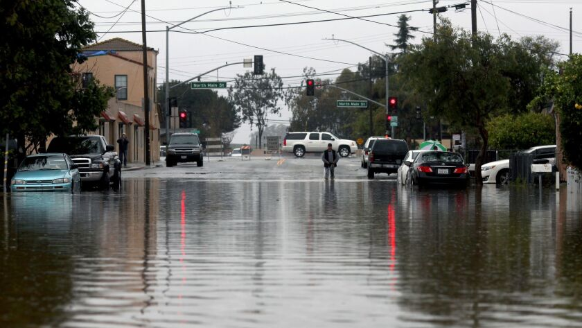 A man walks through floodwaters Monday in Salinas. Forecasters issued flash flood warnings throughout the Bay Area and elsewhere in Northern California.
