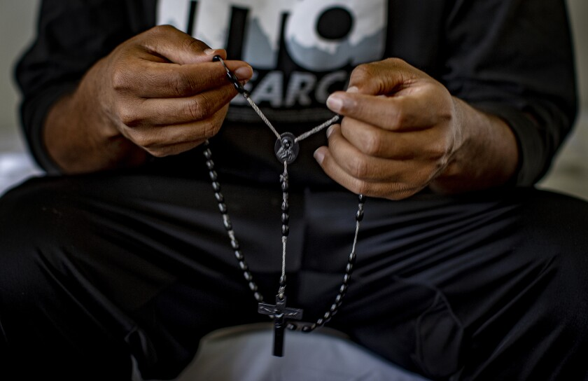 Tsegai, 30, who fled persecution in Eritrea, holds a rosary given to him by family members.
