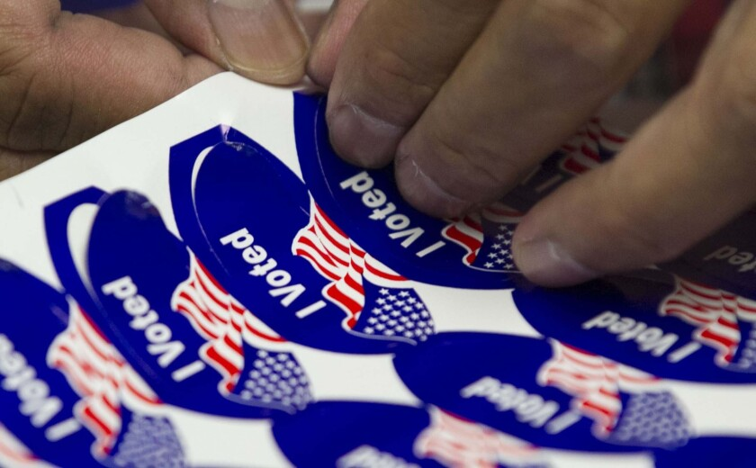 A poll worker peeled off stickers to hand out to voters showing at a San Diego polling station on Election Day in 2018.