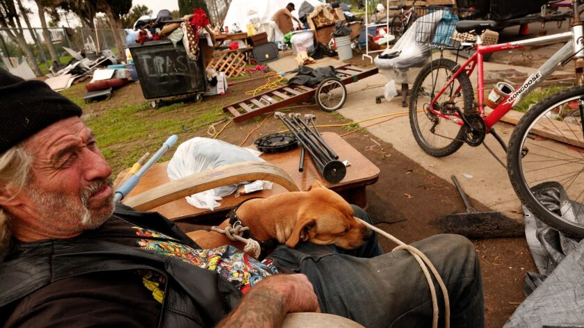 In this January 2017 file photo, Joe Sigler 59, sits with his dog Mojo as his homeless encampment along W. 95th Street  in the Manchester Square neighborhood of Los Angeles.