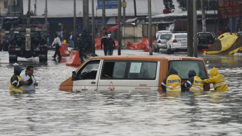 Transit and Civil Protection workers in Mexico attempt to move a van from a flooded street June 14, 2018, as a result of storm Bud in Mexico.