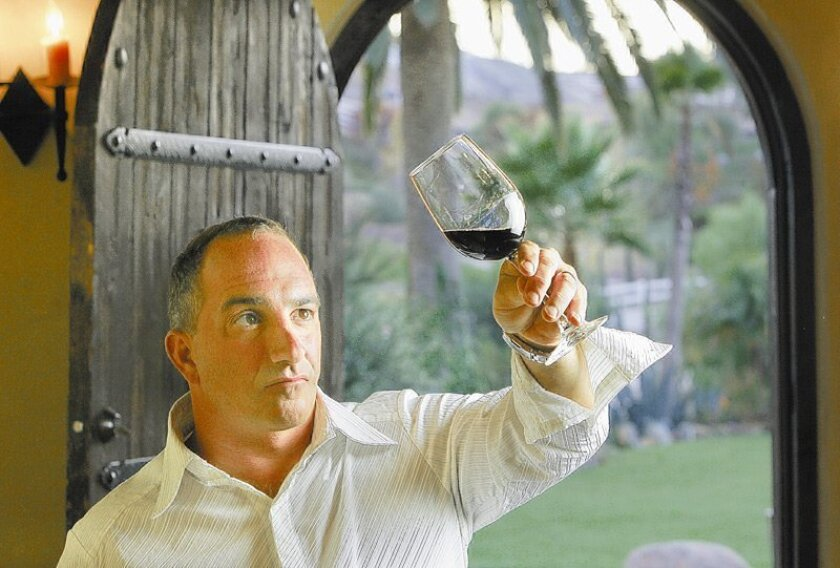 "Former tall ship captain Mike Battiata inspected some of the wine he produced recently in his ""wine cave"" at home in Encinitas."