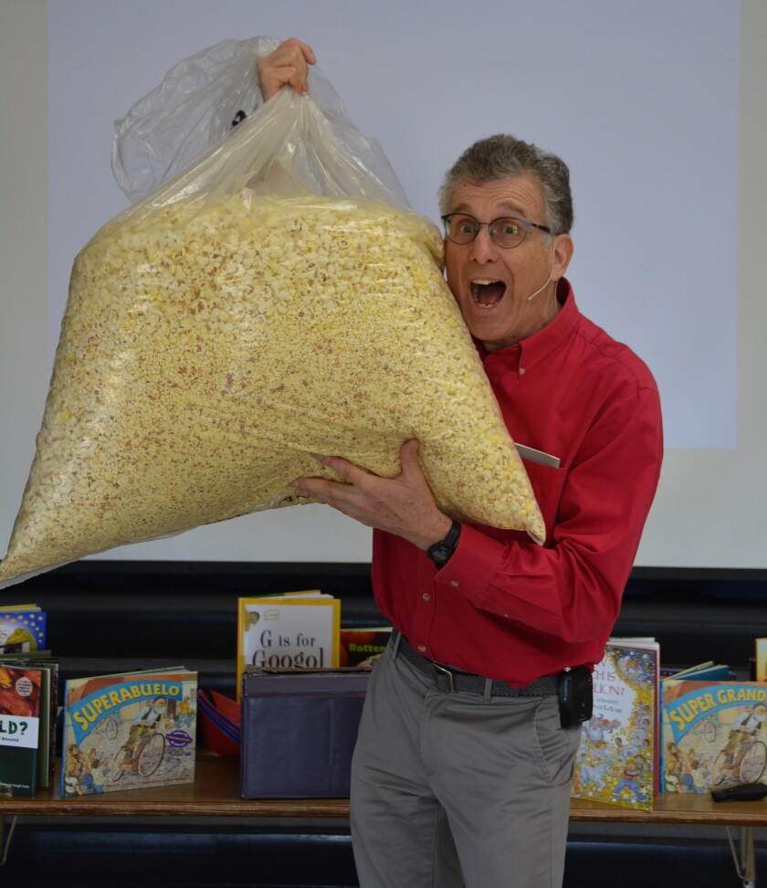 Author David M. Schwartz visited several Escondido schools as part of the Assistance League of Inland North County's Ready...Set...Read! program. Here he's teaching children at Juniper Elementary about the concept of 1 million using 10,000 pieces of popcorn.