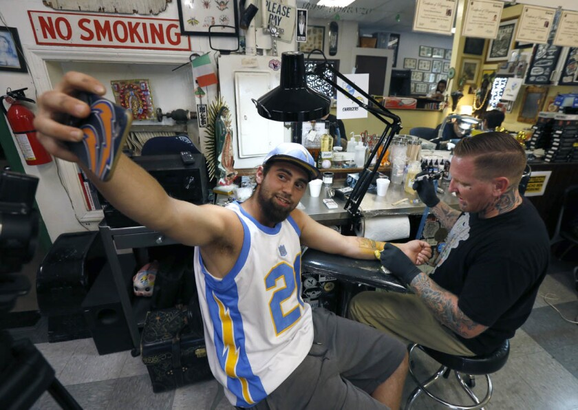 Anthony Cabadas takes a selfie while getting a Charger tattoo from tattoo artist Asa Crow at the Shamrock Social Club in West Hollywood on August 15, 2017. (Glenn Koenig/Los Angeles Times)