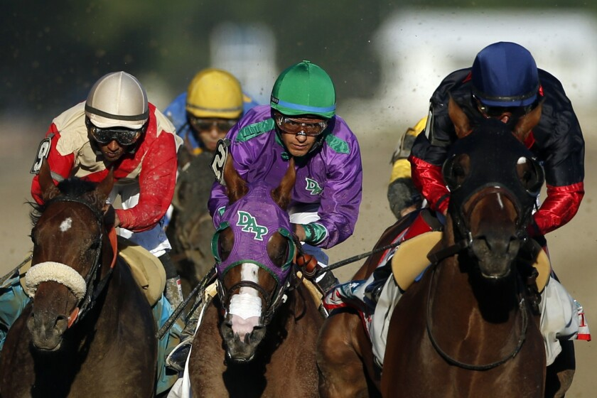 California Chrome, center, is flanked by Wicked Strong, left, and Tonalist, right, as they head down the backstretch of the Belmont Stakes. Tonalist went on to win, denying California Chrome the Triple Crown.