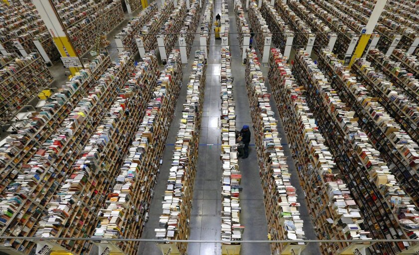 FILE - In this Monday, Dec. 2, 2013, file photo, an Amazon.com employee stocks products along one of the many miles of aisles at an Amazon.com Fulfillment Center in Phoenix. Amazon reports quarterly earnings on Thursday, Jan. 30, 2014. (AP Photo/Ross D. Franklin, File)
