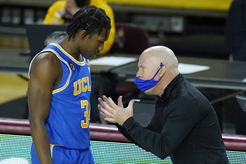 UCLA coach Mick Cronin talks with guard David Singleton.